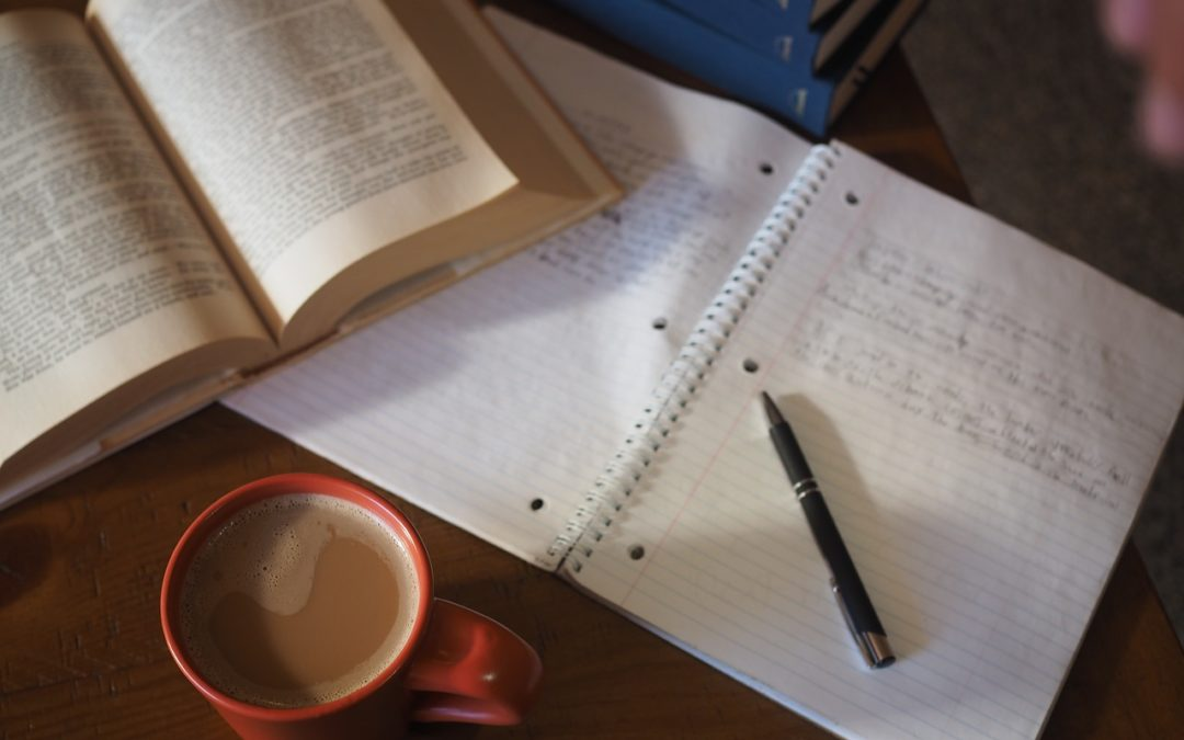 Homework on table with coffee, notepad, book, and pen